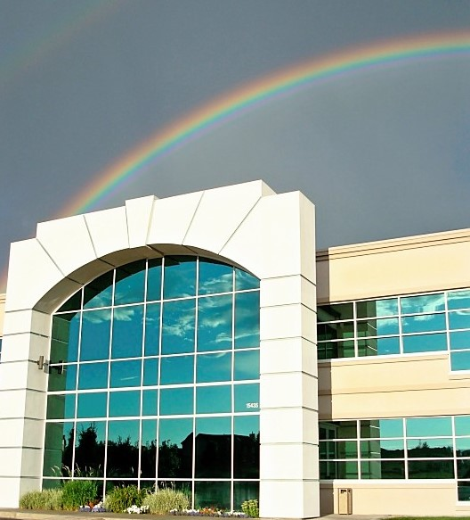 office building front with rainbow in sky above